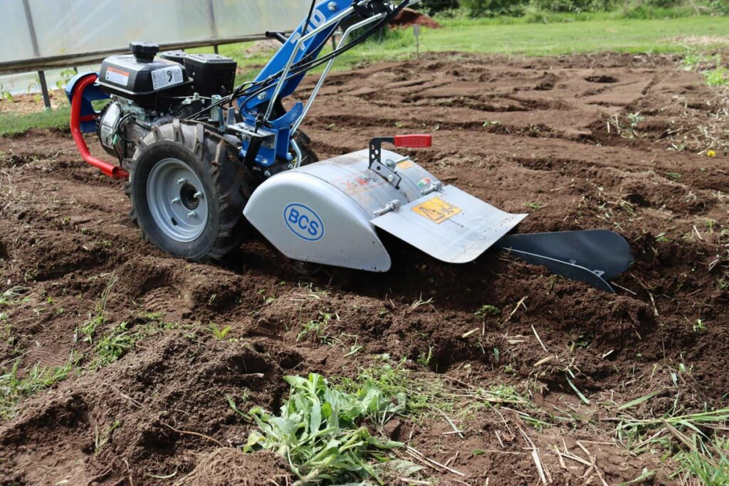 Image of a BCS two-wheel tractor digging a trench.