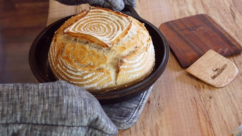 Image of a loaf of freshly made sourdough bread being placed onto a wooden counter.