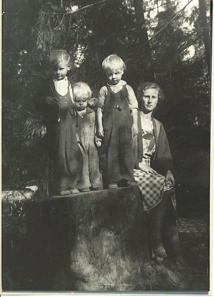 An old black and white photo of a mom sitting on a stump with three small children beside her.