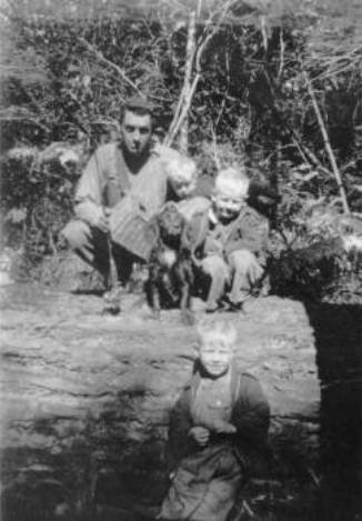 An old black and white photo of a man standing on a log in a creek with 3 kids and a dog beside him.
