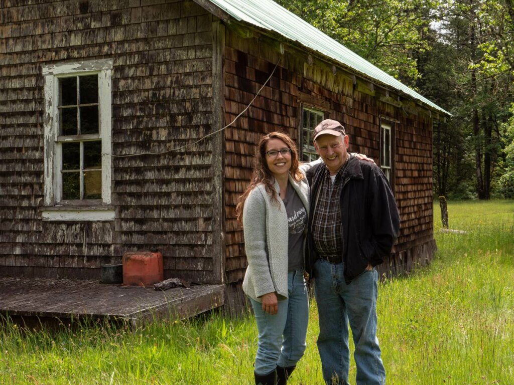 A father and daughter standing in front of an old farmhouse.