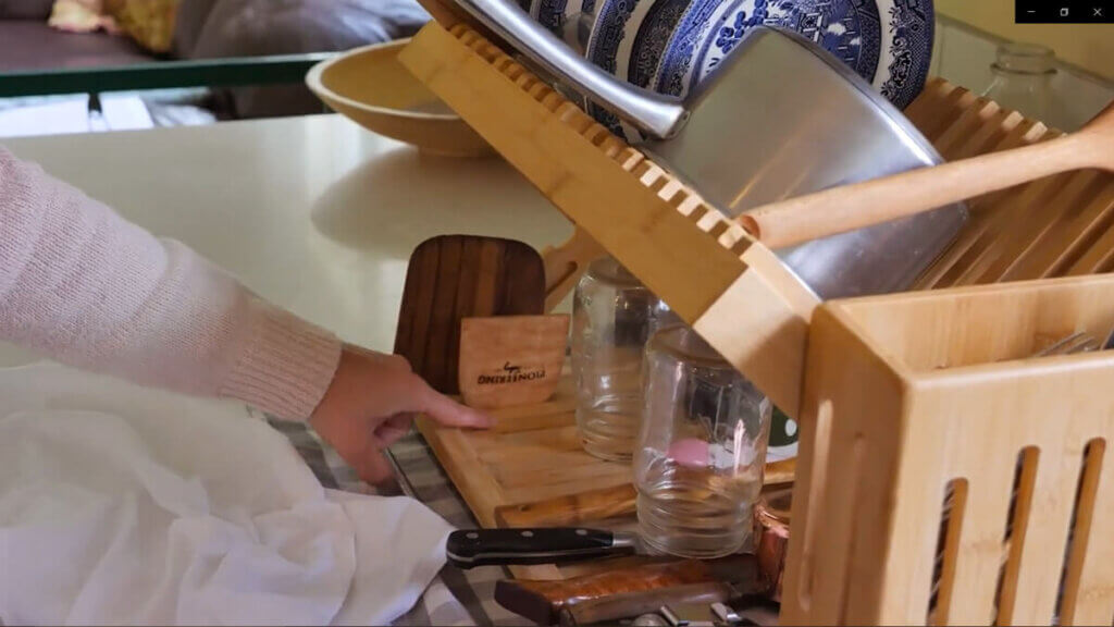 A wooden drying rack with various wooden utensils drying on it.