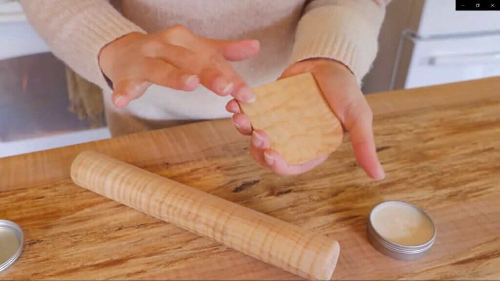 A woman conditioning a wooden dough scraper with wood butter and her hands.