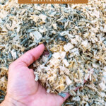 Pinterest pin for using woodchips in the garden. Image of a hand scooping up woodchips.