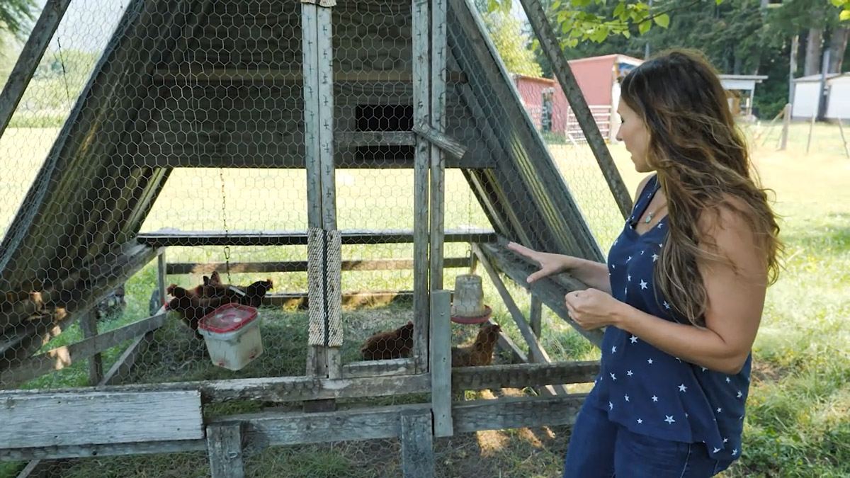 A woman standing beside a mobile chicken tractor with chickens inside.