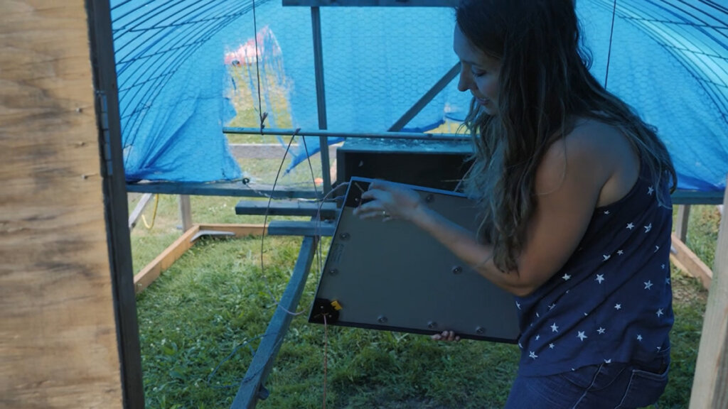 A woman holding up a heat plate inside a mobile chicken coop.