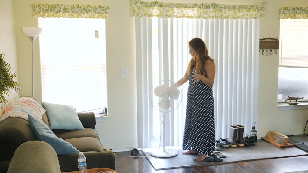 A woman standing in front of a large sliding door with a fan in front of the door.