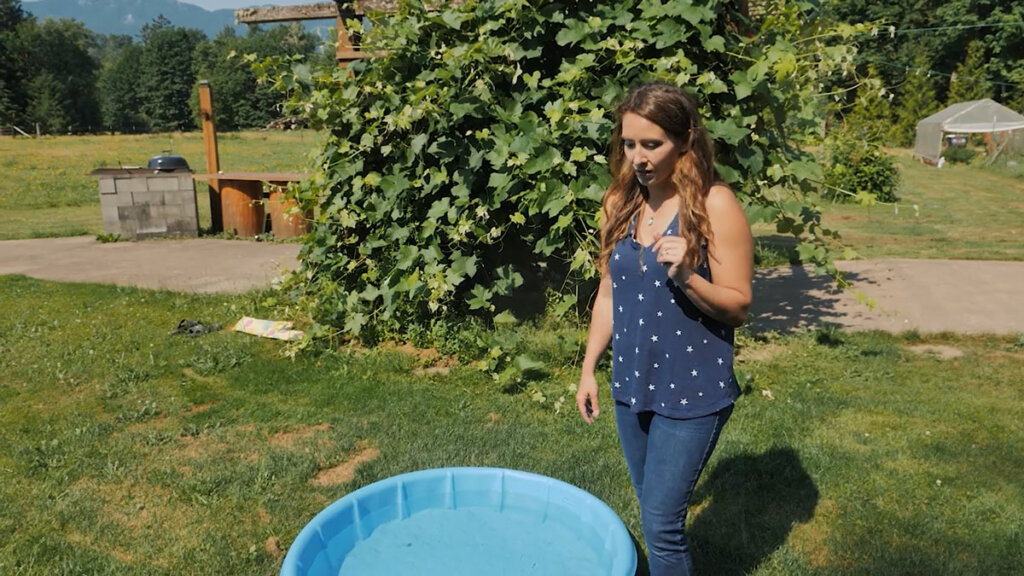A woman standing next to a kiddie swimming pool.