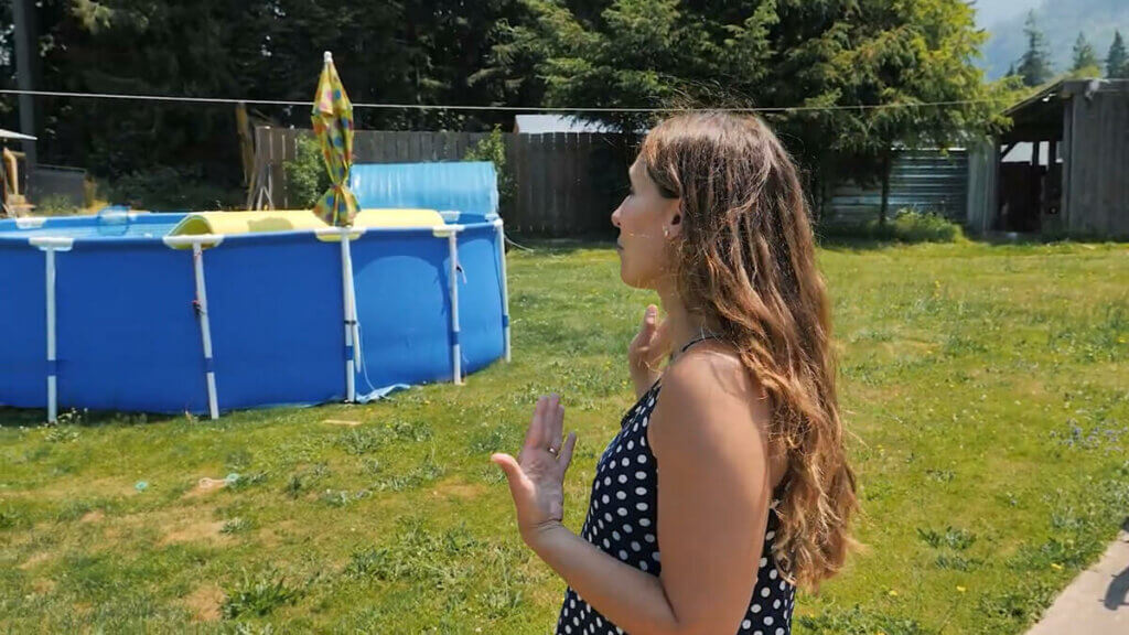 A woman gesturing to an above ground pool.
