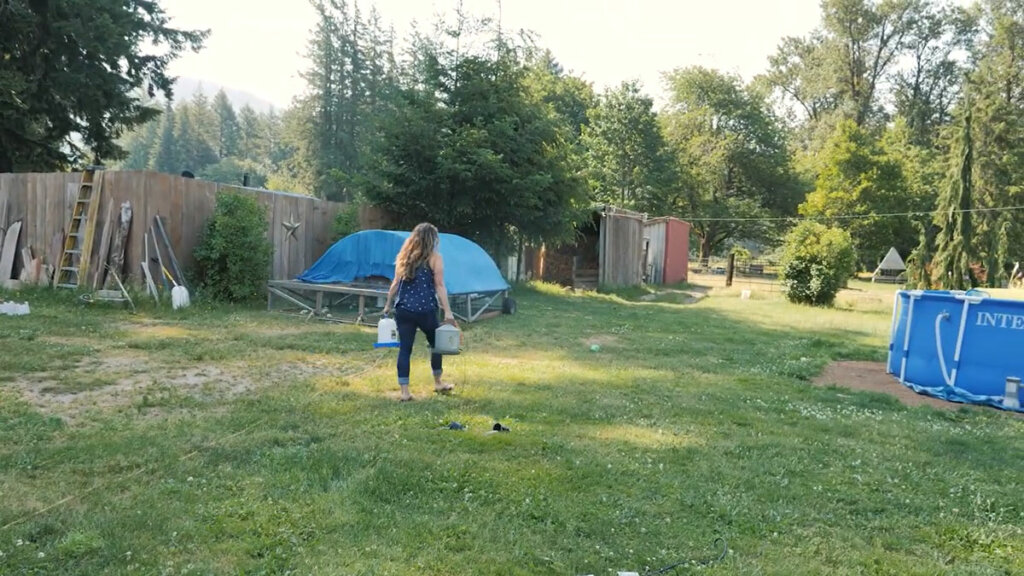 A woman walking through the grass to a mobile chicken tractor carrying two waterers.