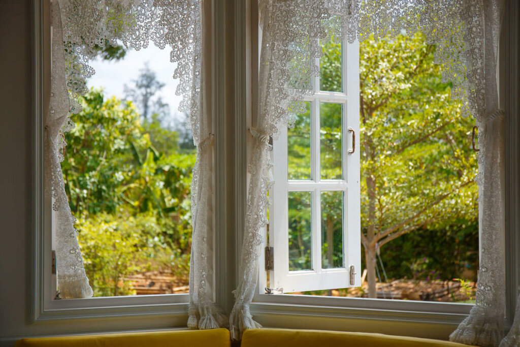 An open window with sheer curtains looking out into a yard.