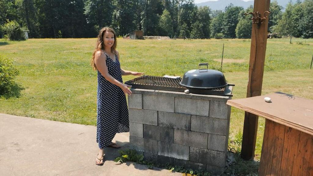 A woman standing beside an outdoor kitchen and cinderblock bbq.