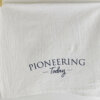 Pioneering Today cotton tea towel handing from wooden clothespins