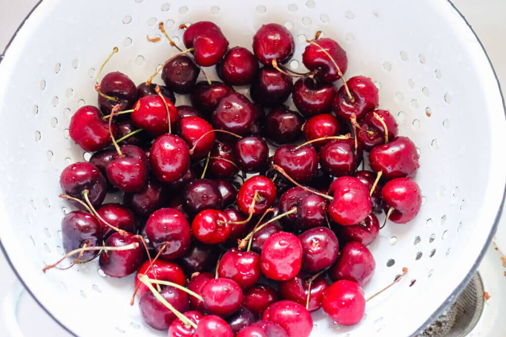 A colander filled with cherries.
