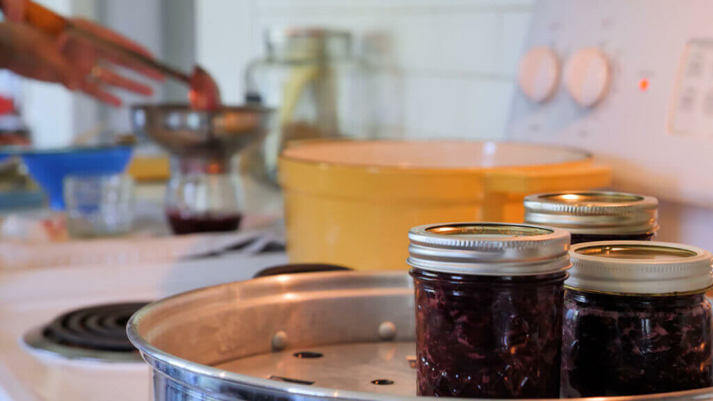 Three jars of cherry jam sitting in a steam canner.