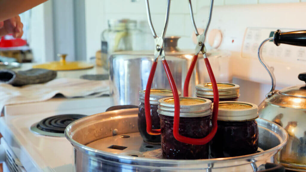 Jar lifters lifting out a finished batch of cherry jam from a steam canner on a stovetop.