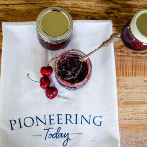 Three jars of cherry jam sitting on a counter with a Pioneering Today tea towel.
