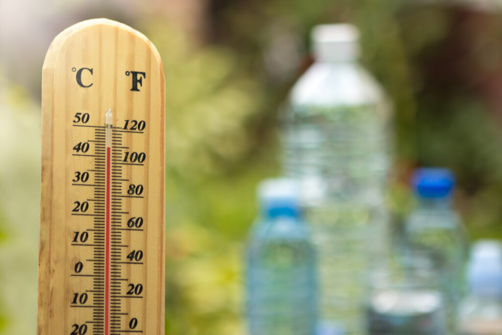 An outdoor thermometer with bottles of water in the background.