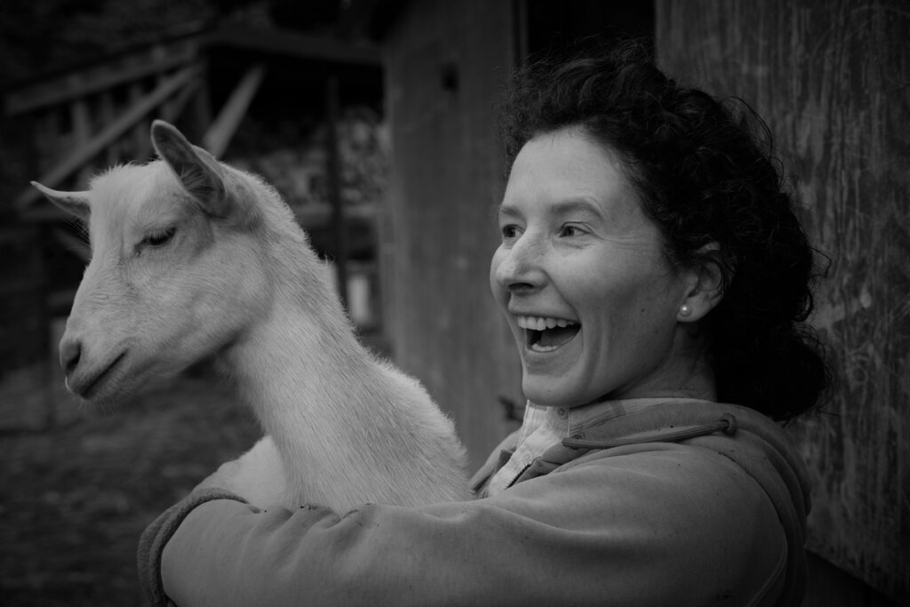 Black and white image of a woman holding a goat.