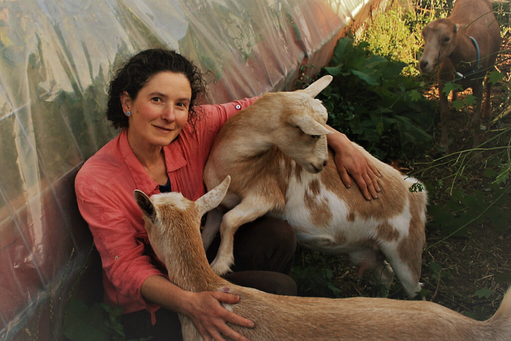 Image of a woman sitting on the ground with two goats.
