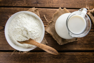 Freeze dried milk powder next to a pitcher of milk.