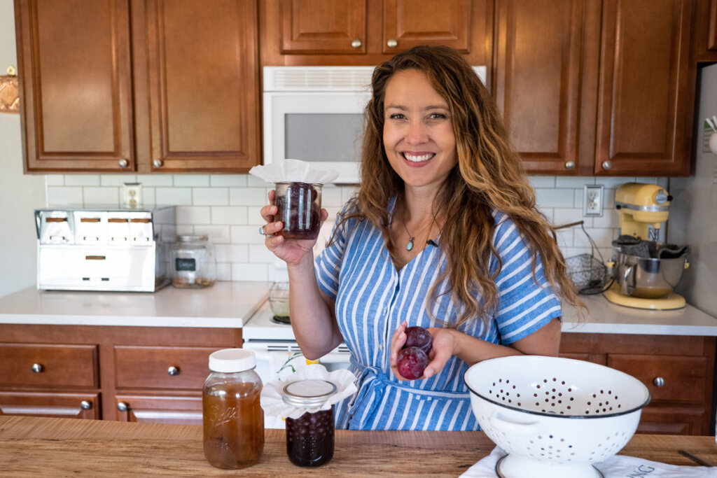 A woman holding a jar of fruit vinegar in the kitchen.