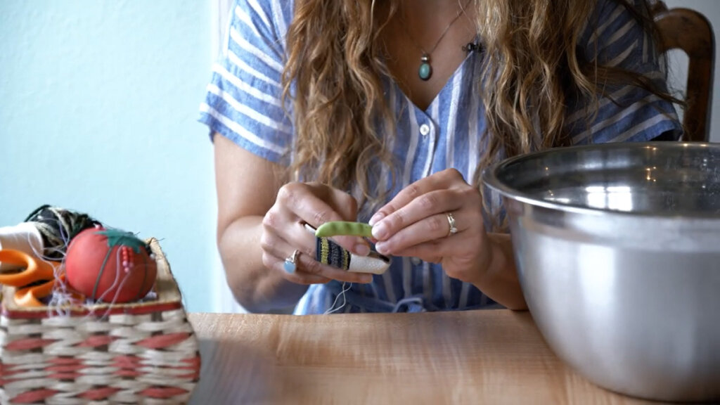 A woman poking a needle through a green bean to make leather britches.