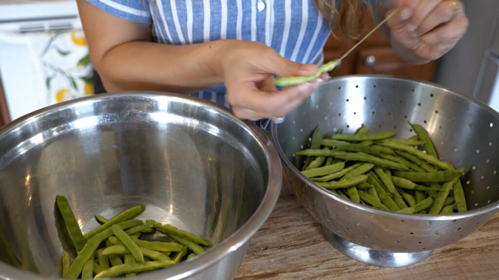 A woman stringing green beans and putting them into a stainless steel bowl.