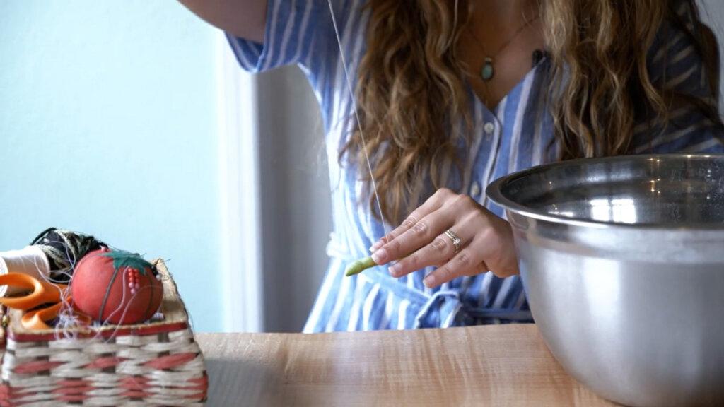 A woman threading a green bean onto a piece of thread.