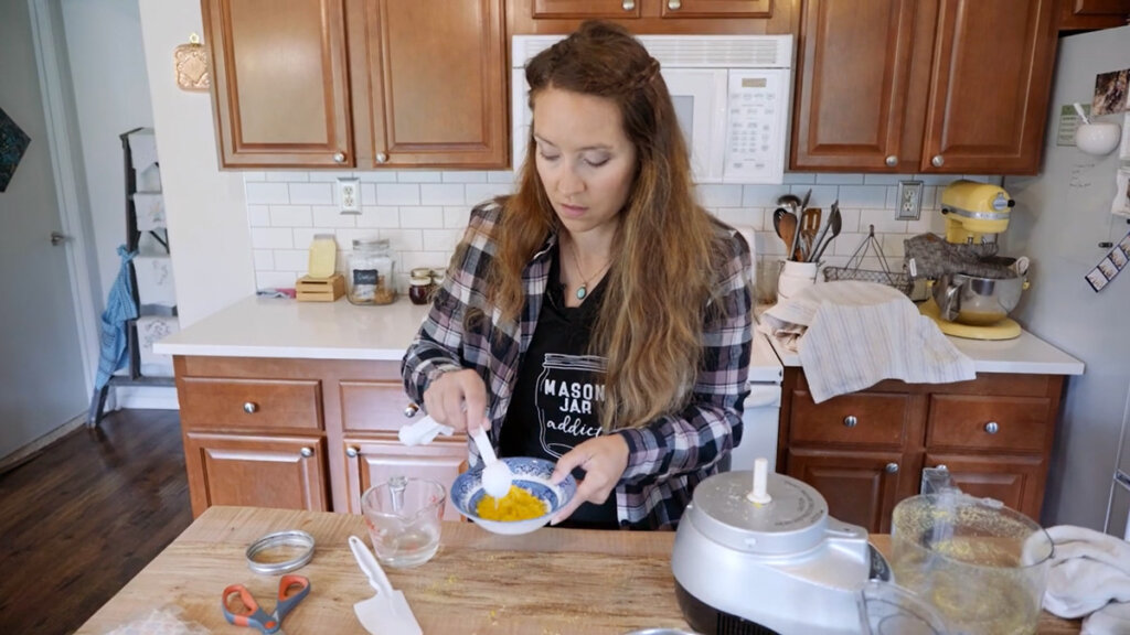 A woman stirring freeze dried eggs that have been reconstituted.