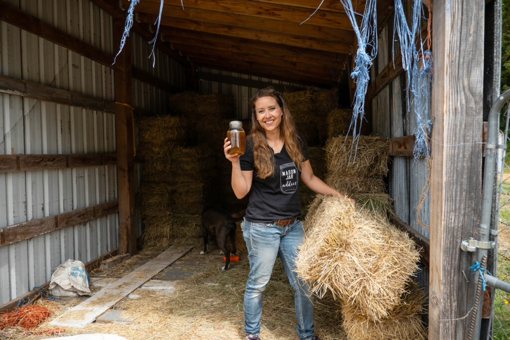 A woman in a hay barn holding up a jar of ginger water.
