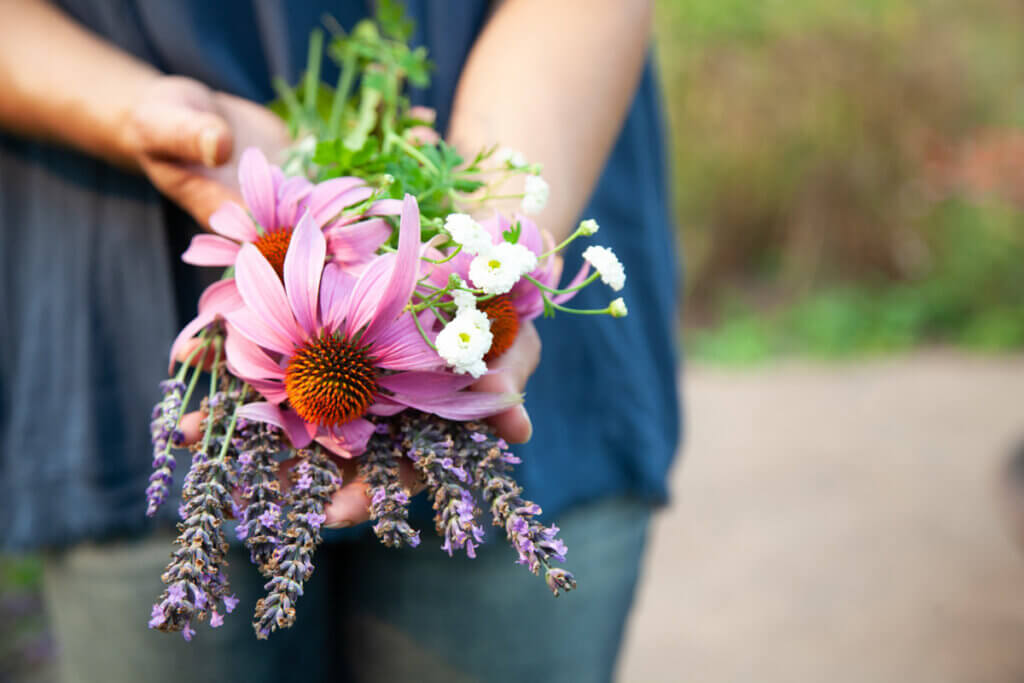 A woman holding a bundle of herbal flowers.