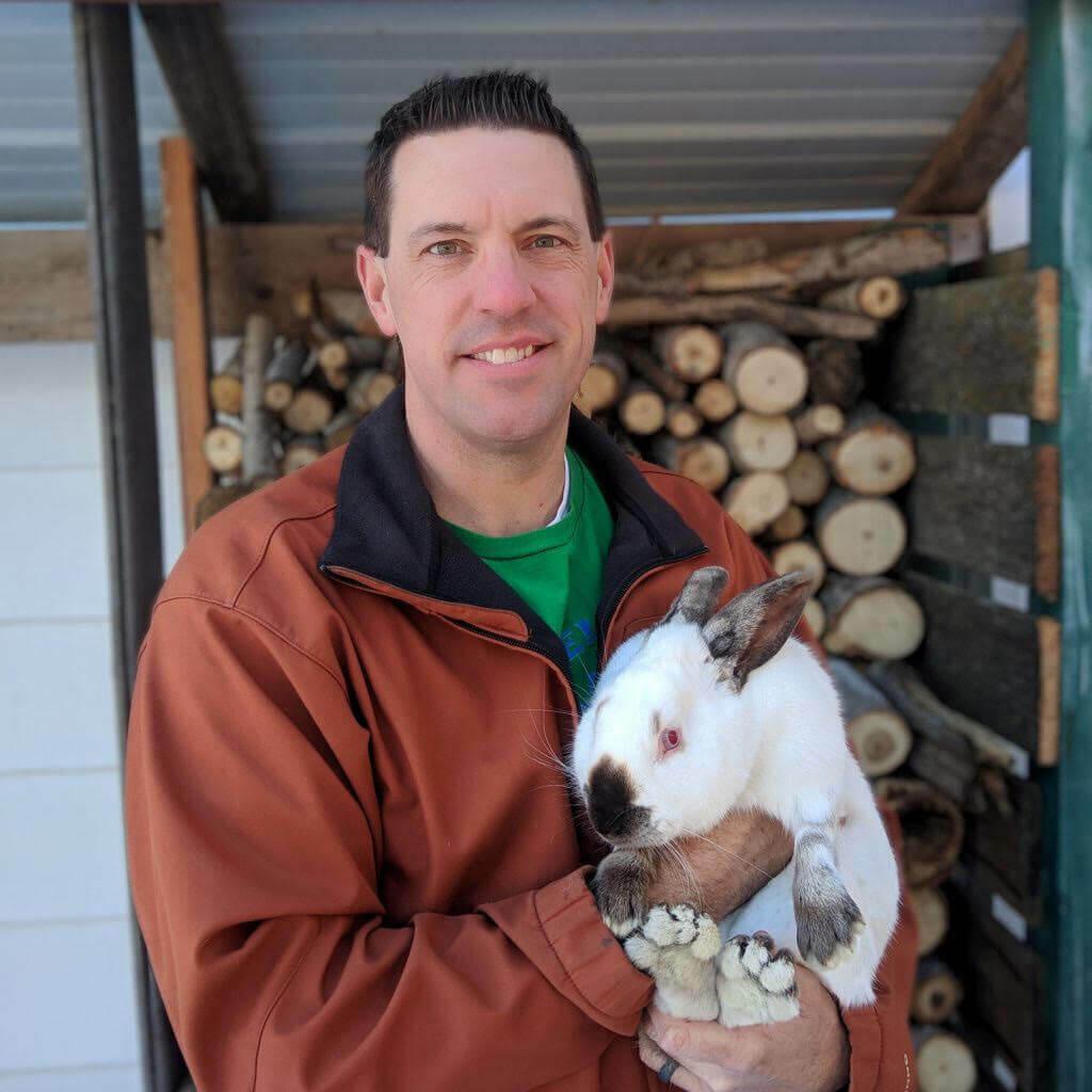 A man holding a large rabbit.