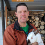 Pinterest pin for raising meat rabbits. Image of a man holding a large rabbit.