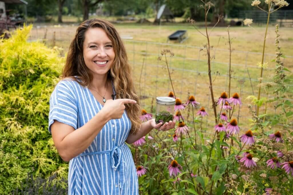 A woman holding a mason jar standing in the garden.