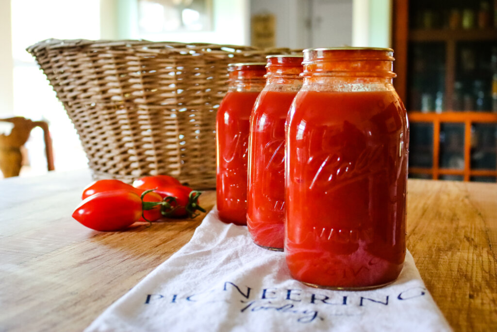 Jars of home canned tomato sauce on counter with ripe paste tomatoes and wicker basket