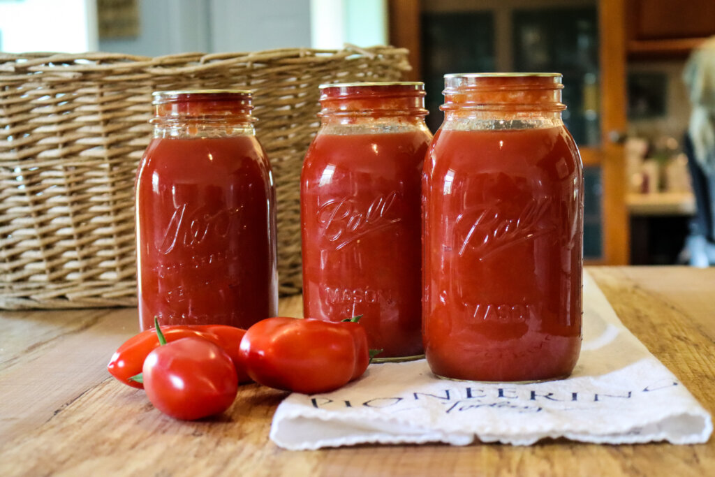 home canned jars of tomato sauce on counter with ripe tomatoes