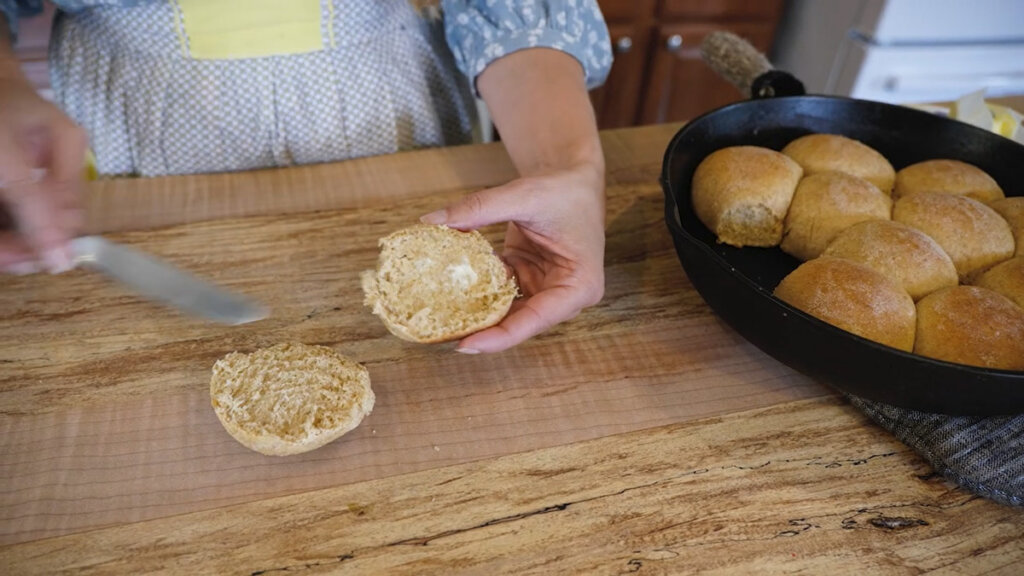 A roll cut in half and spread with butter.