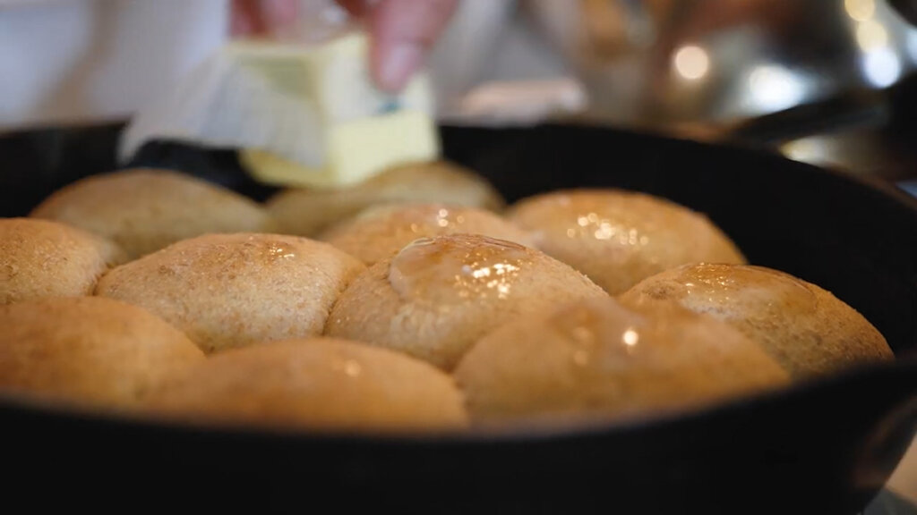 Freshly baked rolls being slathered with butter.