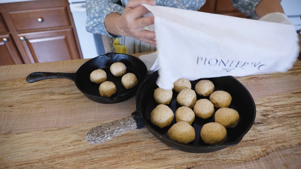 Two cast iron pans with bread rolls being covered with a tea towel to rise.
