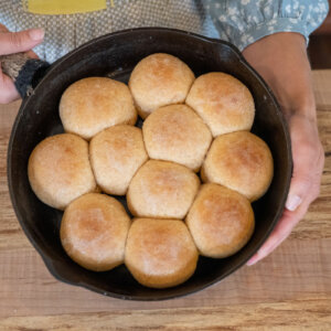 A cast iron skillet with fresh made bread rolls.