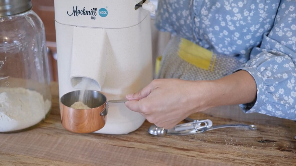 A woman's hands holding a measuring cup catching fresh milled flour from a Mockmill home grain mill.