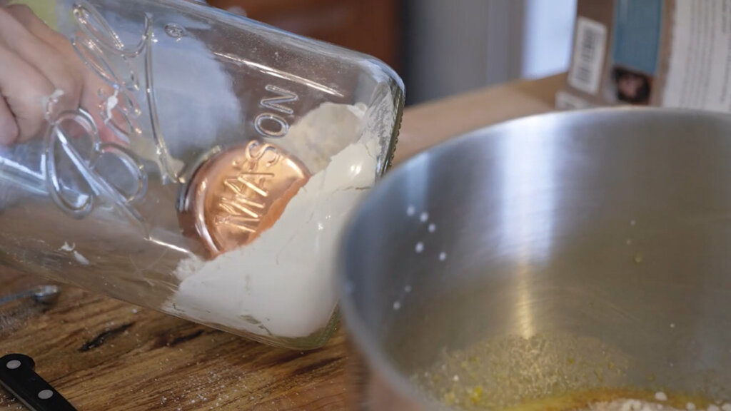 A measuring cup inside a large mason jar getting a scoop of flour.