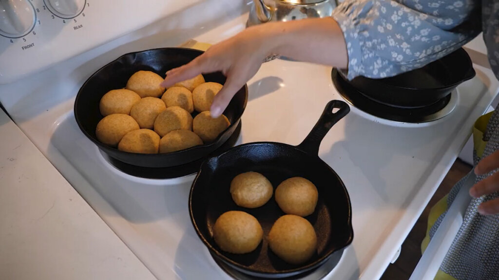 Two cast iron skillets with risen bread rolls sitting on a stovetop.