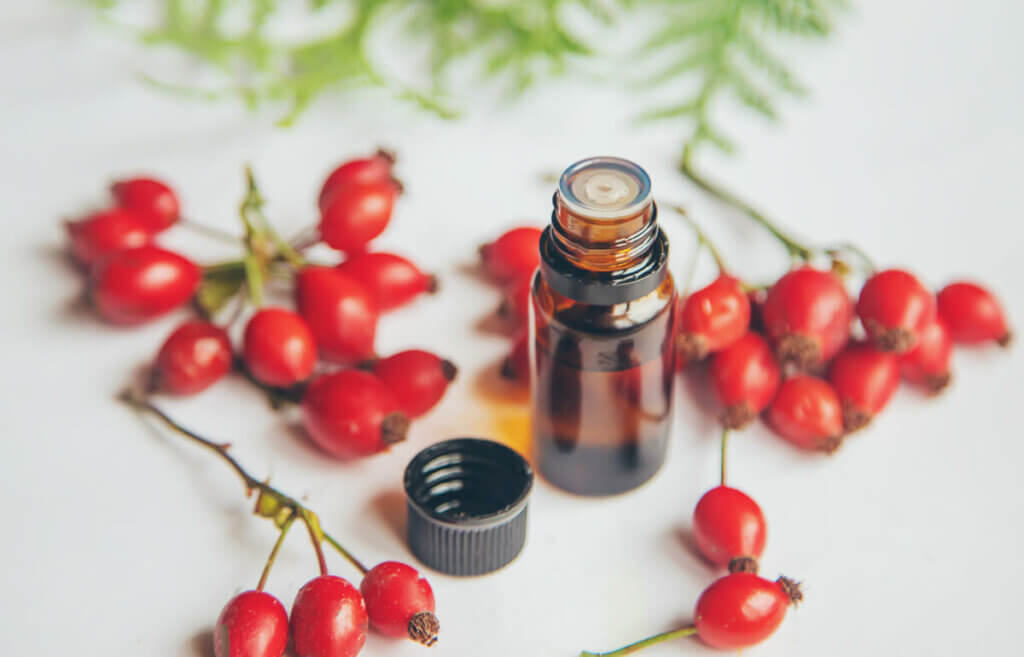 Rosehips on a counter next to a bottle of rosehip essential oil.