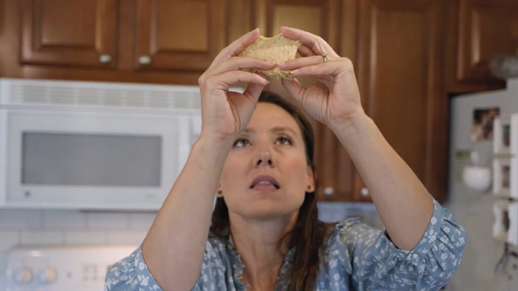 A woman holding a piece of bread dough up doing a windowpane test.